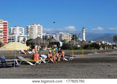 TORRE DEL MAR, SPAIN - OCTOBER 27, 2008 - Tourists sunbathing on the beach with views towards the lighthouse Torre del Mar Malaga Province Andalusia Spain Western Europe, October 27, 2008.