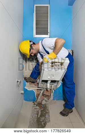 Construction worker destroying flush toilet of a small bathroom.