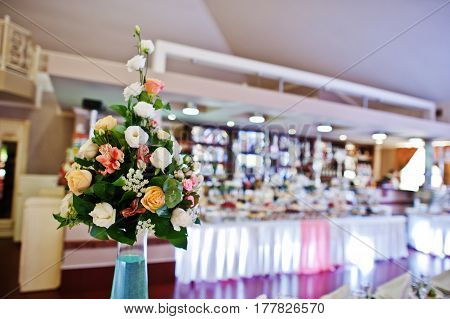 Decor On Wedding Reception, Bouquets Of Flowers On Vase With Blue Water At Tables Of Guests.