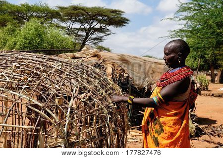 SOUTH HORR KENYA - JULY 07: African woman with characteristic decorative necklaces from the Samburu tribe in the traditional dress he is building his house in Kenya South Horr in July 07 2013