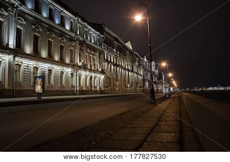 Night view of the granite Palace Embankment in St. Petersburg from Kamenoostrovsky bridge. House AP Gagarin architect Quarenghi D. cobblestone road and night lights