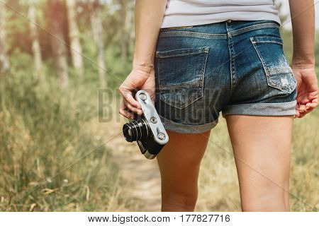 Close-up of female trekker holding old camera and walking on the road in natural park. Concept of vacation, excursion and lifestyle.
