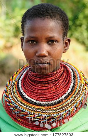 SOUTH HORR KENYA - JULY 08: Young African girl from the Samburu tribe with characteristic decorative necklaces on the market in Kenya South Horr in July 08 2013