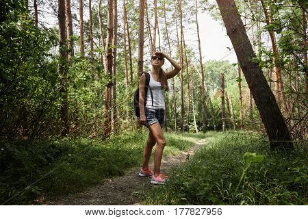 Active woman with backpack hiking in the wood. Concept of traveling and tourism.