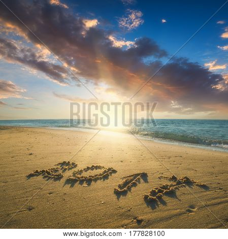 Year 2017 written in sand on a sea beach. Majestic sunrise with beautiful clouds in a sky.