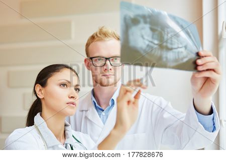 Two dentists analysing denture with x-ray image
