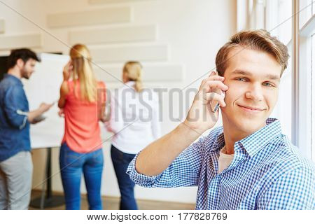 Young man as student calling with smartphone during meeting