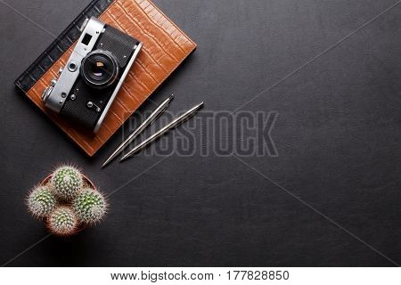 Office desk with photo camera, notepad, pen and pencil. Top view with copy space
