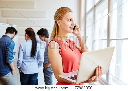 Young woman calling on the phone next to her start-up team with her smartphone and laptop