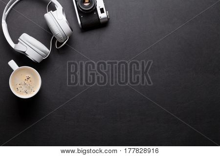 Office leather desk table with headphones, camera and coffee. Top view with copy space
