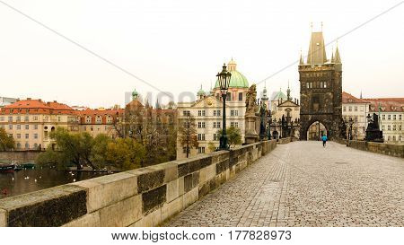 Lonely runner at Charles bridge in morning jogging at sunrise.