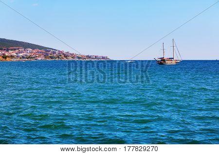 Picturesque seascape. Black Sea coast. Pleasure yacht and shore on the horizon.