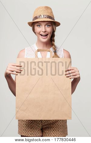 Beautiful excited surprised woman wearing summer straw fedora hat holding craft bag with empty copy space