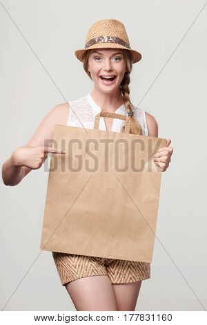Beautiful excited woman wearing summer straw fedora hat holding craft bag with empty copy space and pointing at it