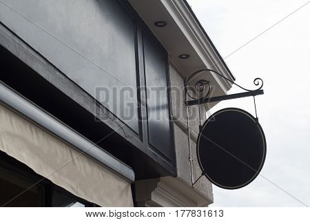 Horizontal front view of black empty round signage on a building with classical architecture