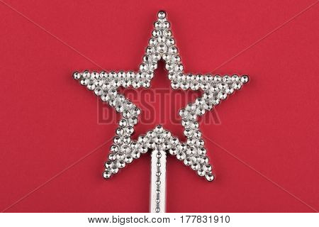 front view of crystal shiny star wand on red background selective focus