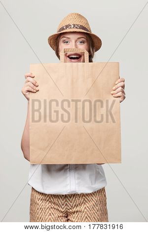 Happy playful woman wearing summer straw fedora hat holding craft bag with empty copy space