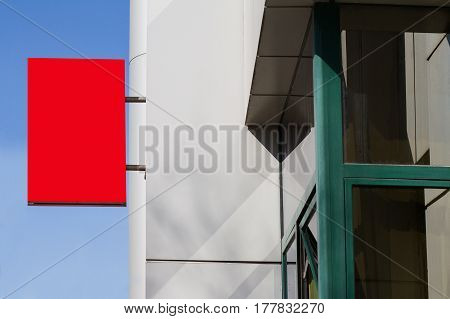 horizontal side view of empty red square signage on the exterior of a building