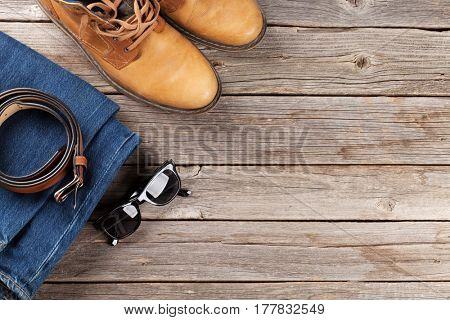 Men's clothes and accessories. Jeans, shoes, glasses on wooden background. Top view with copy space