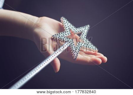 horizontal side view of a child hand holding a star shaped silver magic wand on dark background selective focus