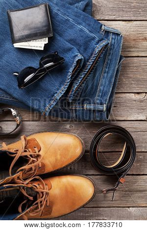 Men's clothes and accessories. Jeans, shoes, glasses, wallet with cash on wooden background. Top view