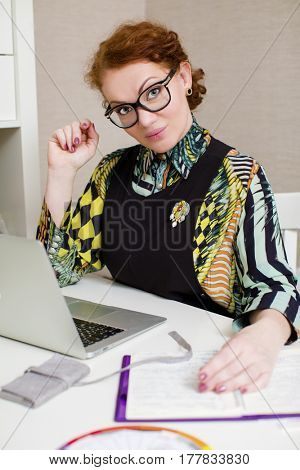 Stylish middle-aged lady using laptop at home