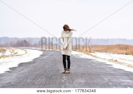 Girl in the midle of winter rural road. Country road among frosted trees.
