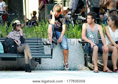 Oslo Norway - July 22 2014: teenagers relax in the park Eidsvolls Plass located on the main street Karl Johans Gate