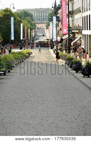 Oslo Norway - July 22 2014: People walk Oslo's main street Karl Johans Gate at center with the Royal Palace in the background