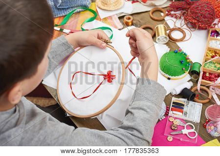 boy embroidered on the hoop, hand closeup and red ribbon on white textile, learns to sew, job training, handmade and handicraft concept