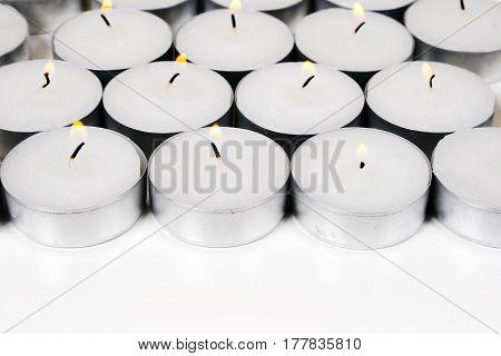 Group of burning round candles on white background