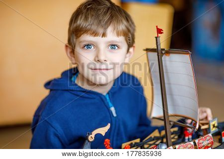 Little blond preschool kid boy playing with toy ship indoors. child with missing teeth in front having fun after school at nursery. Happy boy building and creating toys.