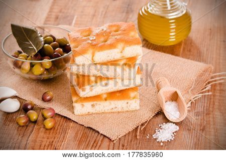 Focaccia bread and olives on cutting board.