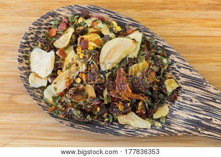 Wooden spoon of dried spicy red chili flakes, sliced garlic, parsley to make Italian Spaghetti aglio e olio