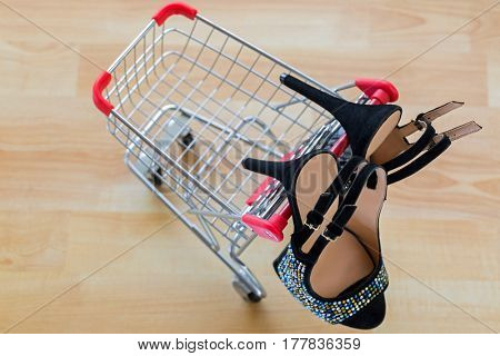 Pair of beautiful black velvet high heel shoes for ladies hanging on mini shopping push cart, on wooden background