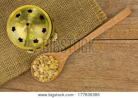 Wooden spoon of aromatic yellow resin gum next to brass incense burner on wood. Incense from Sudanese Frankincense tree made by slashing bark of Boswellia sacra in Etiopia (Boswellia Papyrifera)