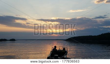 Picture of sunset on lake with floating boat andpeople