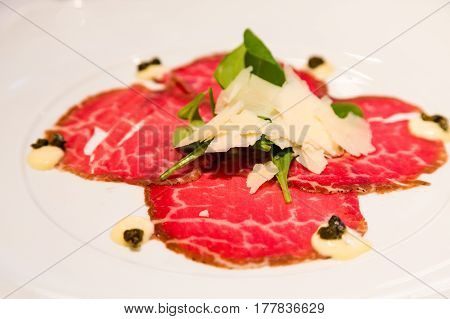 Carpaccio with Shaved Parmesan garnished with Arugula