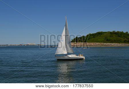 White sailboat sailing off the Boston Harbor Islands in Massachusetts.