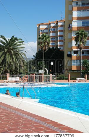 LAGOS, SPAIN - OCTOBER 27, 2008 - People relaxing in an apartment complex swimming pool Lagos Malaga Province Andalusia Spain Western Europe, October 27, 2008.