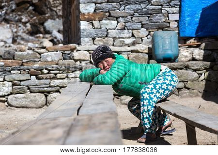 Portrait of Nepalese Girl in traditional colorful Pants and Down Vest relaxing on wooden Bench leaning on Table. Kothey Lodge, Nepal, Solo-Khumbu region, November 3, 2016