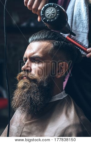 Bearded man with long beard brutal caucasian hipster with moustache getting hair styling with blow dryer and comb by hairdresser at barbershop