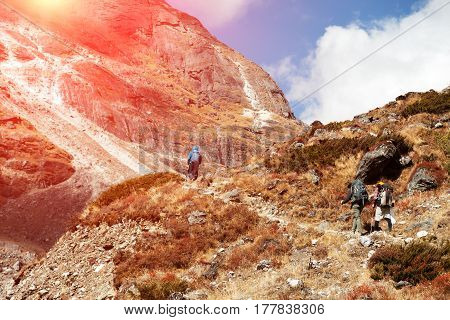 Group of People of different age and ethnicity walking up on Mountain Trail towards Pass throw the Cliff during Hike in Nepalese Himalaya bright Sun shining.