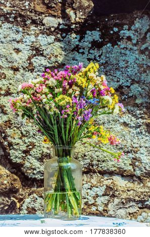 Beautiful colorful bunch of fresh field wild blossoming flowers in bright summer colors in glass jar on sunny day on grey moss or lichen rock background