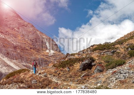 Sunny Mountains View rocky Trail and Hiker in red Jacket and blue Pants walking up carrying backpack and using trekking poles