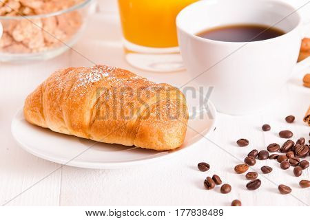 Breakfast with croissants and orange juice on white dish.