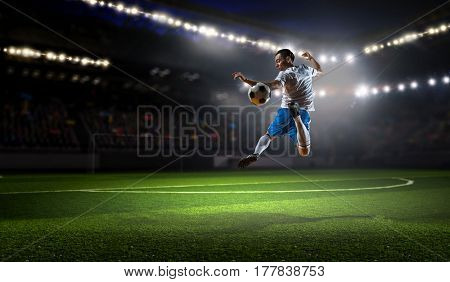 Soccer player at sport arena . Mixed media