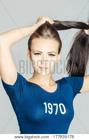 Pretty girl or beautiful woman with long brunette hair ponytail in stylish blue tshirt with 1970 number numeral print design posing on grey background