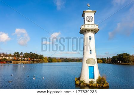 Public Roath Park with Lake Boat House Boats and Robert Scott Memorial Lighthouse in Cardiff Wales UK. Photo taken in March 2017.