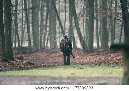 Photographer walking on a path in forest.